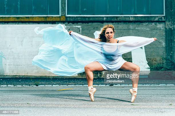 Female ballerina makes a pose and stands on her toes