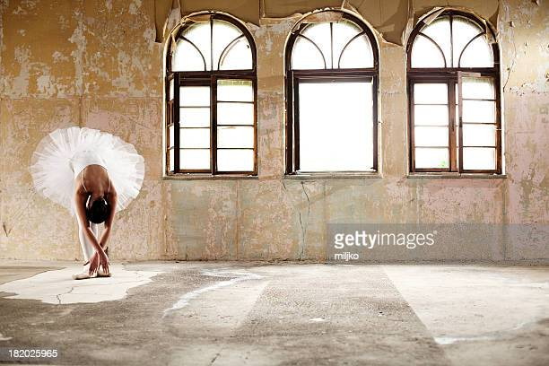 A female ballerina posing by a set of windows