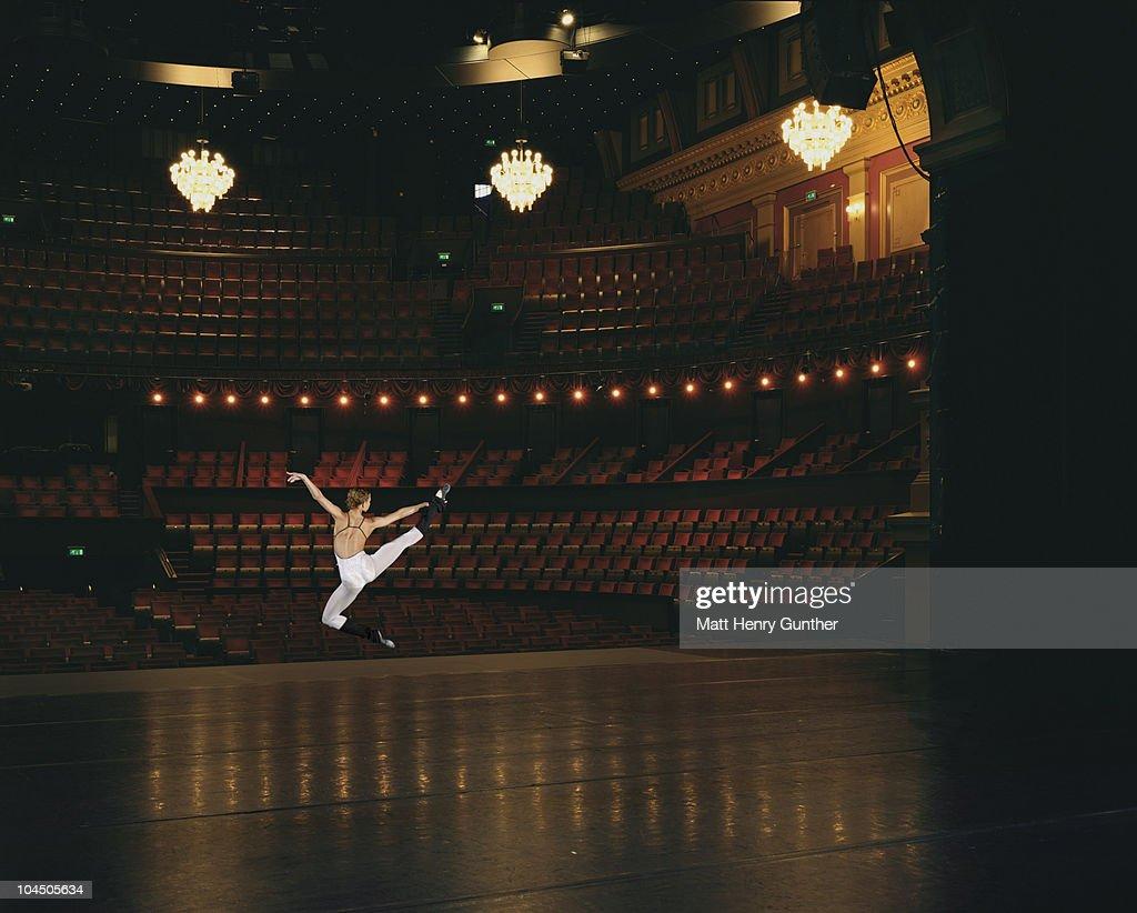 Female ballet dancer jumping onstage