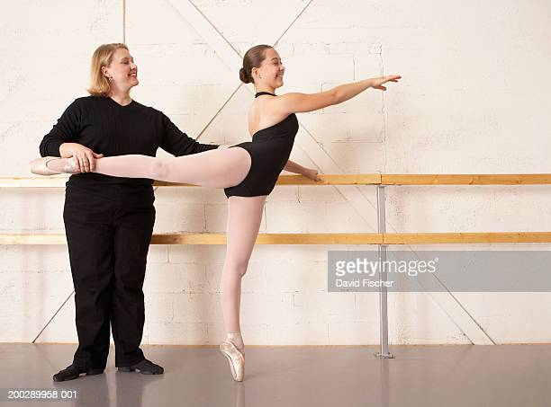 Female ballet instructor helping girl (12-14) with ballet pose