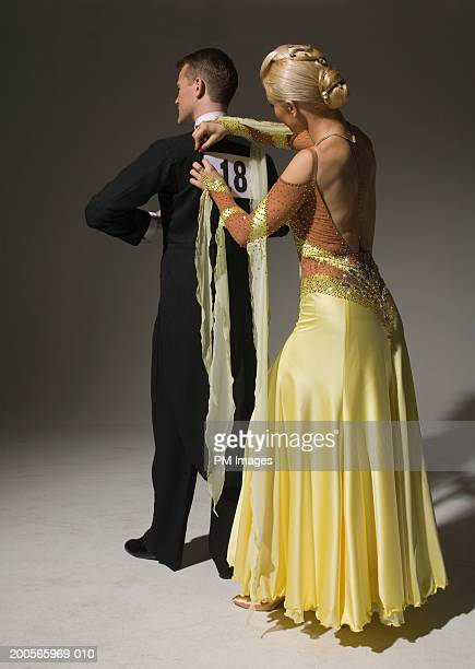 Female ballroom dancer pinning number to partner's back