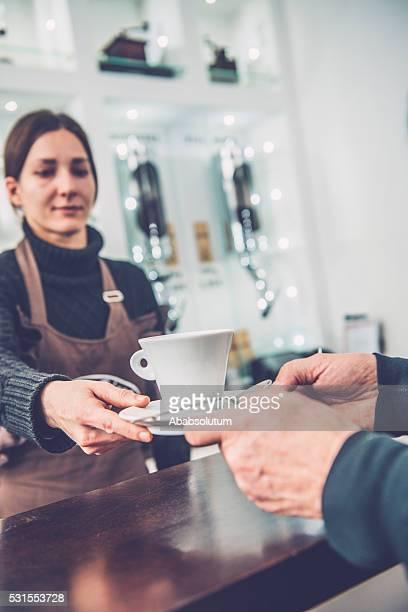 Female Barista Giving Coffee to Senior Man, Caffe Trieste, Europe