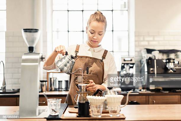 Female barista preparing coffee at counter