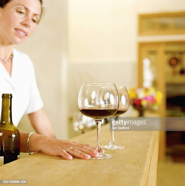 Female bartender lining up wine glass on counter