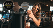 Beautiful young woman pouring beer into the glass. Female bartender tapping craft beer in bar.
