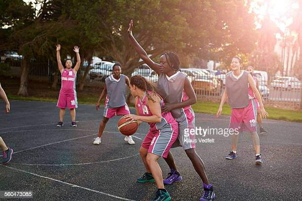 Female basket players dribbling and tackling