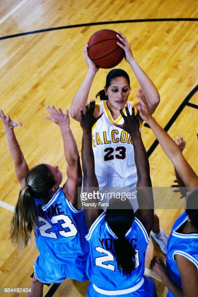 Female Basketball Player Guarded by Three Opponents