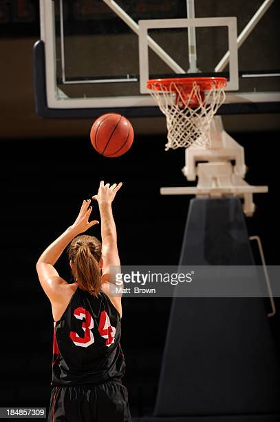 Female basketball player throwing a free throw toward basket