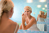 Female beauty, beautiful young caucasian woman applying cream on face in bathroom at home