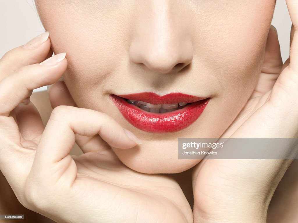 Female beauty, close up on hands and lips : Stock Photo