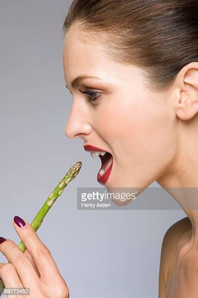 Female beauty model eating asparagus