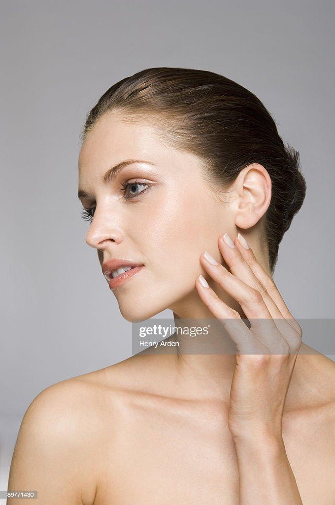 Female beauty model touching skin : Stock Photo