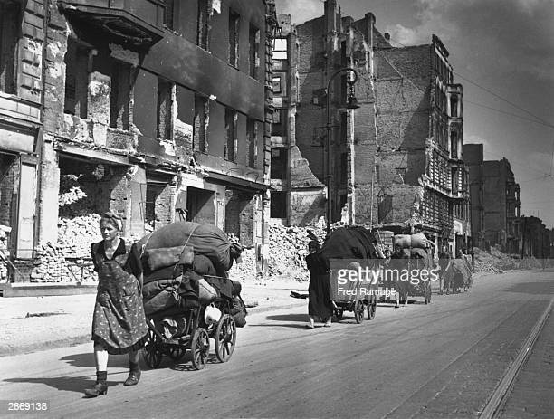 Female Berliners pulling large carts loaded with sacks and possessions through the bombdamaged streets of Berlin Large amounts of baggage such as...
