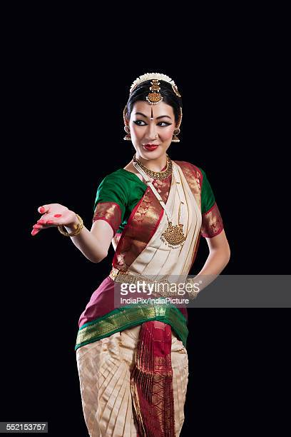 Female Bharata Natyam performer over black background