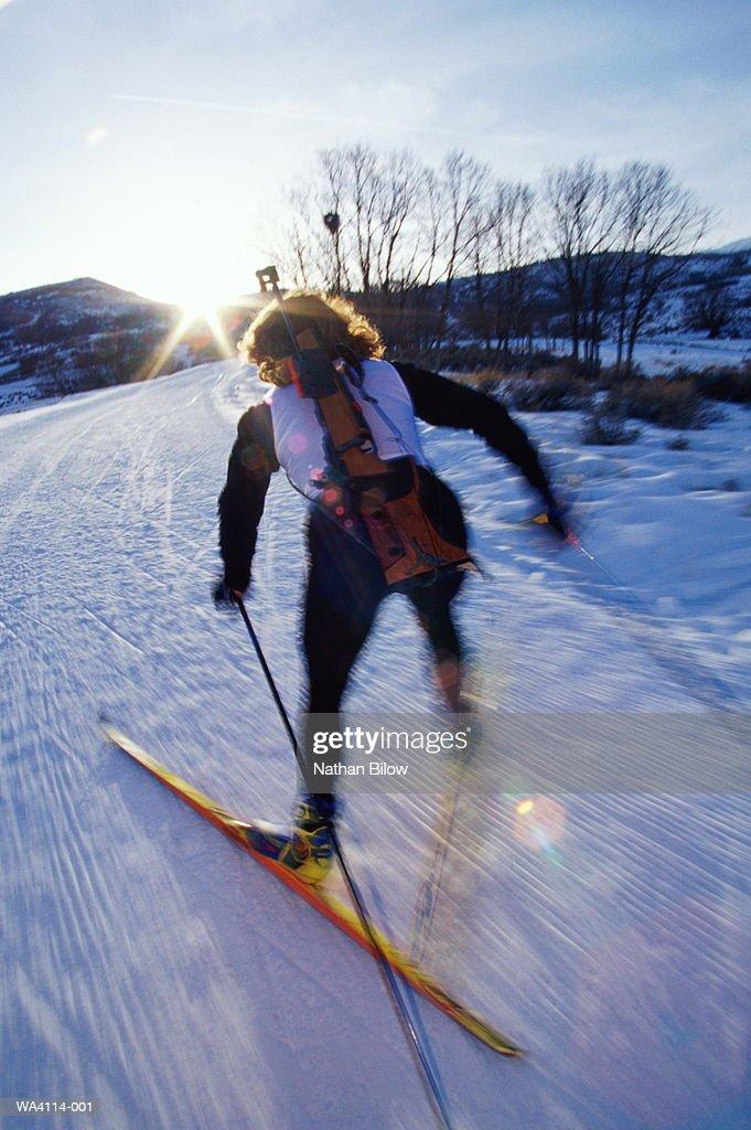 Female biathlete cross country skiing, rifle on back
