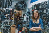 Female Bicycle Mechanic. Female technician in her bicycle repair shop. Portrait of young female mechanic in bicycle store