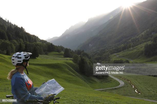 Female bicyclist pauses on mountain roadside