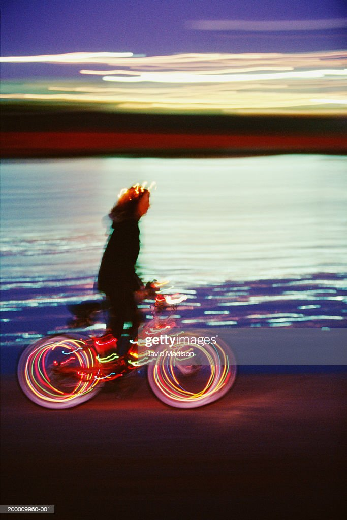 Female bicyclist riding at dusk (long exposure) : Stock Photo