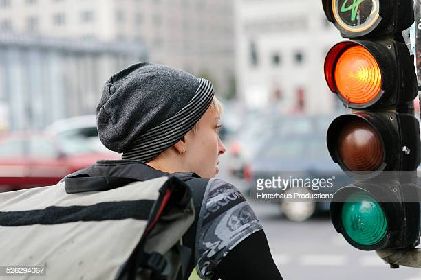 Female Bike Messenger Waiting At Traffic Light