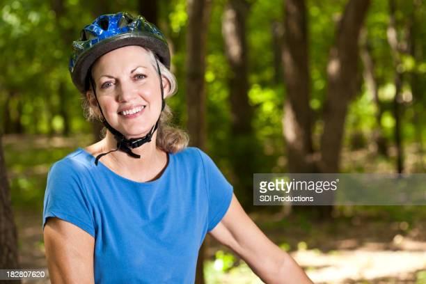 Weibliche bike rider trägt einen Helm und mit einem Lächeln