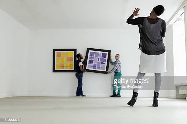 Female black Gallery owner hanging a picture