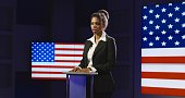 Confident African-American woman holding press conference while standing alone on podium with background of American flag on screen.