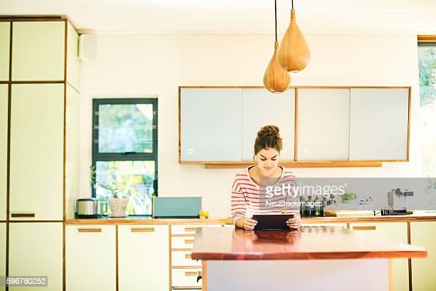 Female blogger using digital tablet at kitchen island