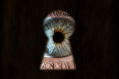 Female blue eye looking through the keyhole. The concept of voyeurism, curiosity, Stalker, surveillance and security