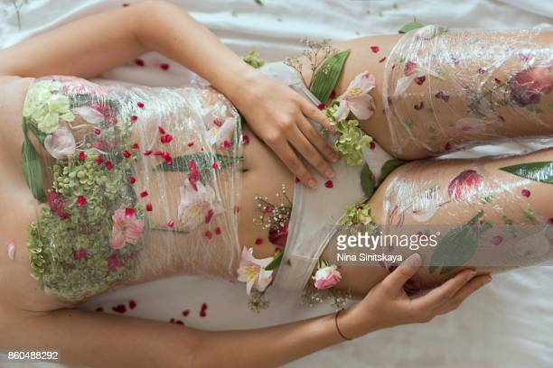 Female body covered with flowers and plastic