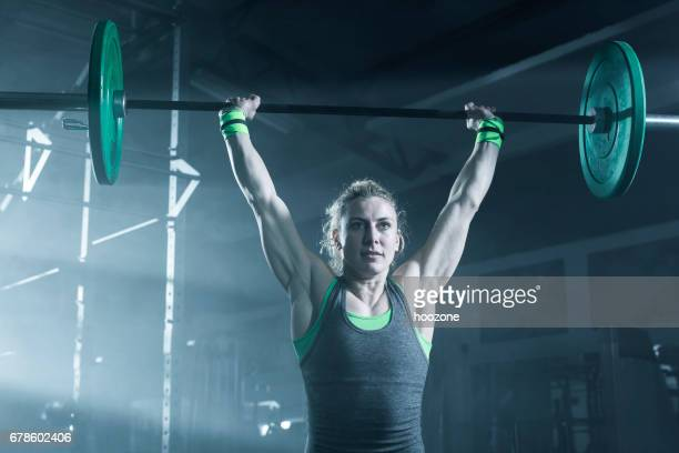 Female bodybuilder doing exercise with weights in gym