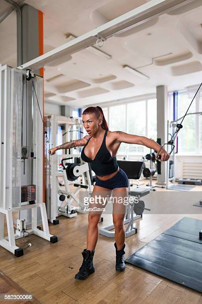 Female bodybuilder training with weight lifting machine at the gym