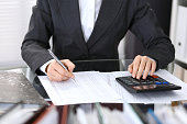 Female bookkeeper or financial inspector  making report, calculating or checking balance. Internal Revenue Service checking financial document. Audit concept in business.