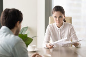 Young business lady holding papers looking at a man with anger, female boss found a mistake in documentation and demanding explanation, male manager can be fired because of his paperwork failure