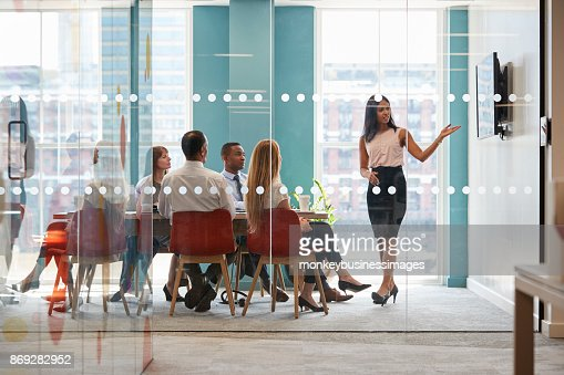 Female boss shows presentation on screen at business meeting : Stock Photo