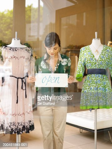 Female boutique owner placing open sign on window