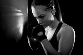 Studio shot of female boxer on the defensive guard next to boxing bag, Black and white.