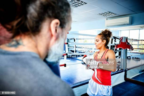 Female boxer getting ready to hit the bag in gym