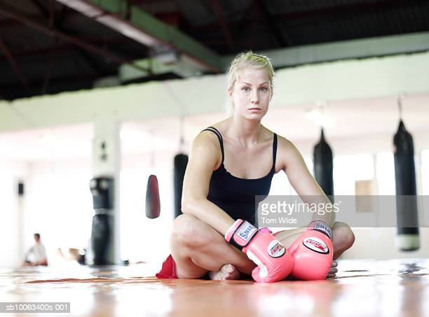 Female boxer sitting  on crash mats in gym, portrait