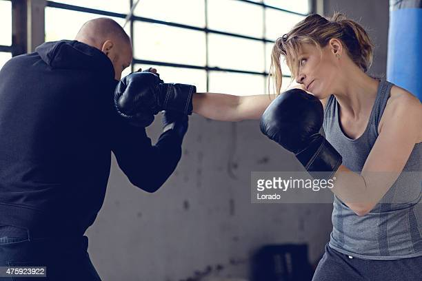 Female boxer sparring with her trainer