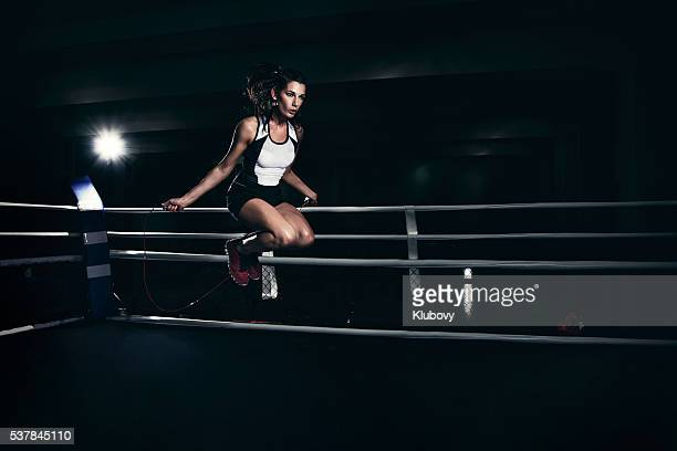 Female boxer training in a boxing ring