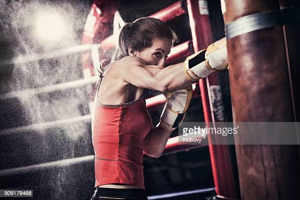 Hembra boxeador capacitación con una bolsa de boxeo