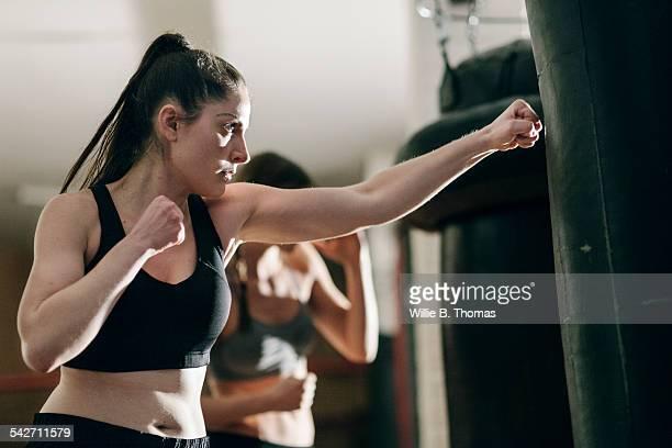Female Boxer training with punching bag