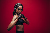 Tough black woman with headphones standing in fighting stance. African female boxer exercising on red background