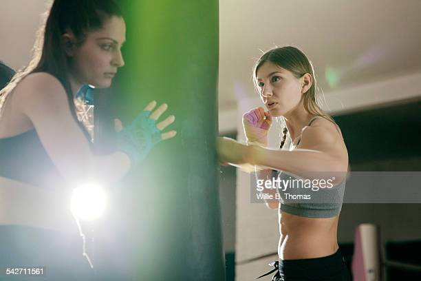 Female boxer working with trainer in gym