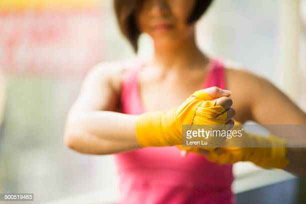 Female boxer wrapping hand bandages in gym.