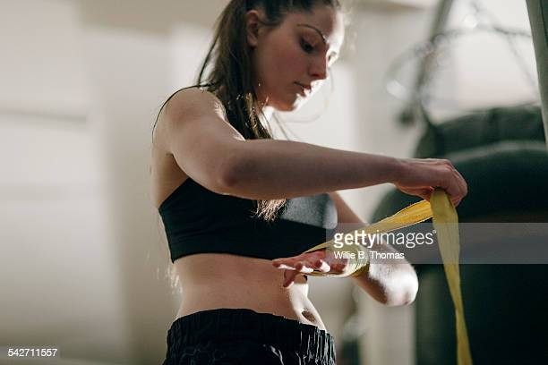 Female boxer wrapping her hands in gym