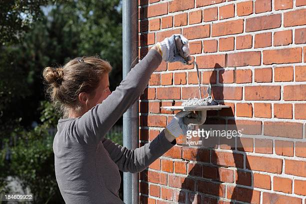 Female bricklayer cementing repairs on exterior house wall