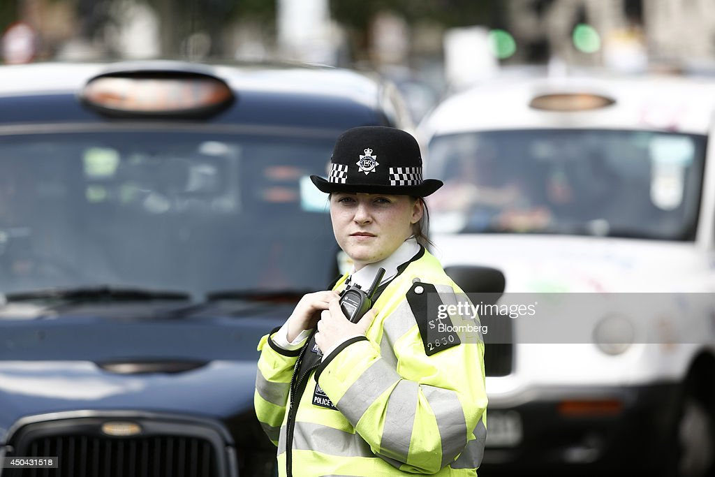 A female British police officer stands on duty as London taxi cabs stand parked on Whitehall, during a protest against Uber Technologies Inc.'s car sharing service in London, U.K., on Wednesday, June 11, 2014. Traffic snarled in parts of Madrid and Paris today, with a total of more than 30,000 taxi and limo drivers from London to Berlin blocking tourist centers and shopping districts. Photographer: Simon Dawson/Bloomberg via Getty Images