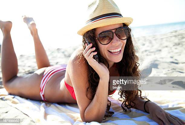 Female brunette in hat and bikini on a beach on the phone