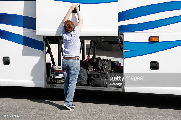 Female Bus Driver Lifting Luggage Storage Door